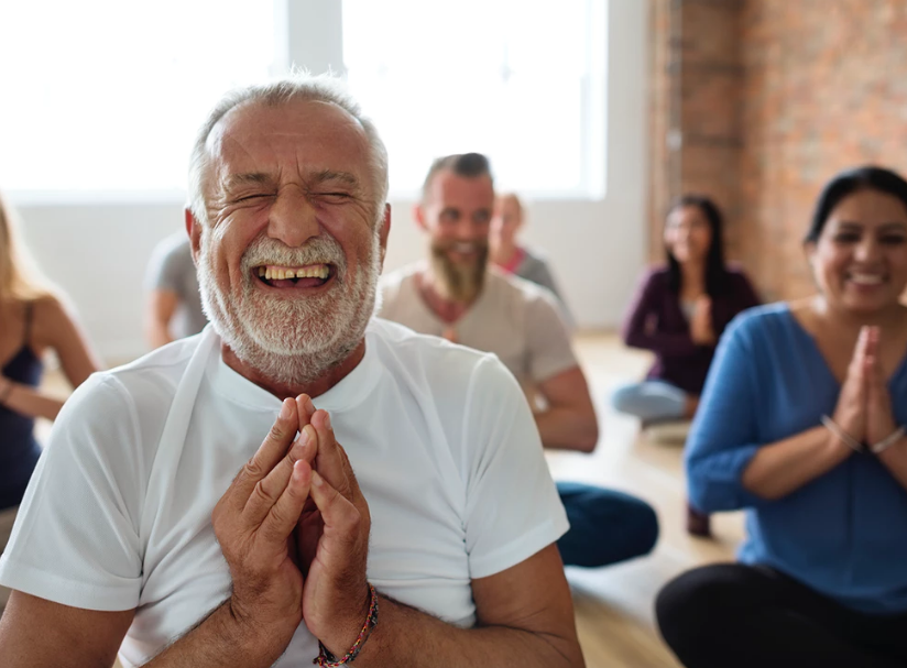 old man in white shirt smiling and squinting with eye closed doing yoga and laughing mind body and soul good for the heart stock photo