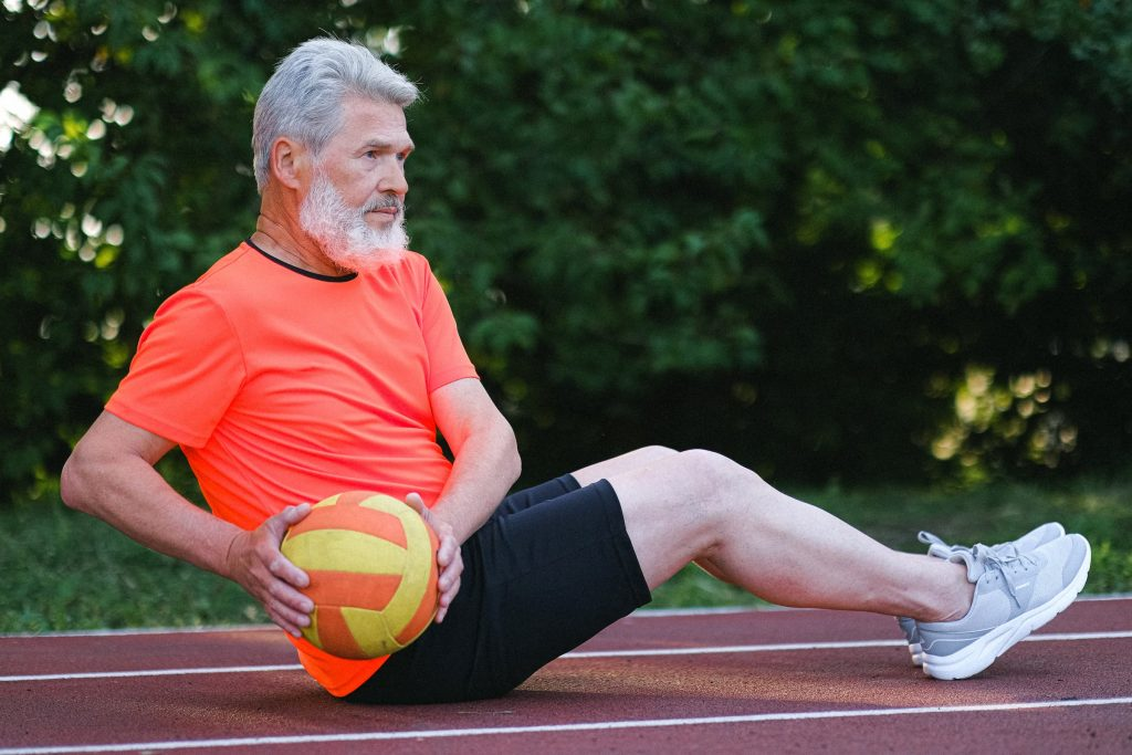 active white senior man in orange shirt and black shorts working out while sitting on outdoor track with exercise ball
