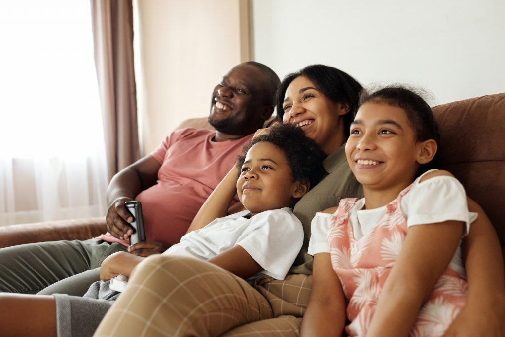 black hispanic family sitting on couch looking at tv television off into the distance watching super bowl game