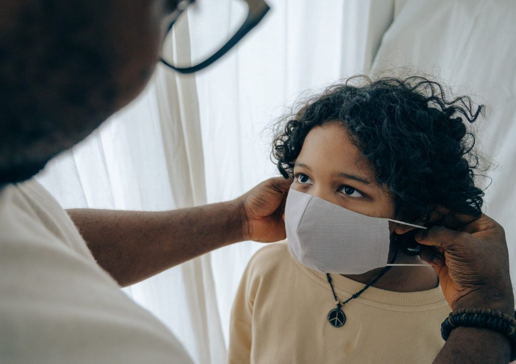 dad putting mask on son's face everyone wear a mask during super bowl party