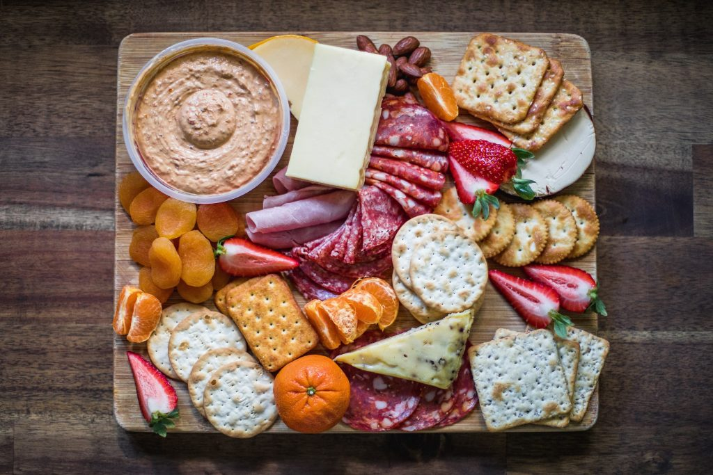 birds eye photo of cheese platter with hummus, crackers, different cheeses and healthy snacks for super bowl party