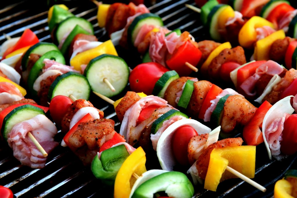 Up close shish kabobs with cucumbers, tomatoes, shrimp, chicken, bacon, yellow peppers, green peppers, onions and red peppers