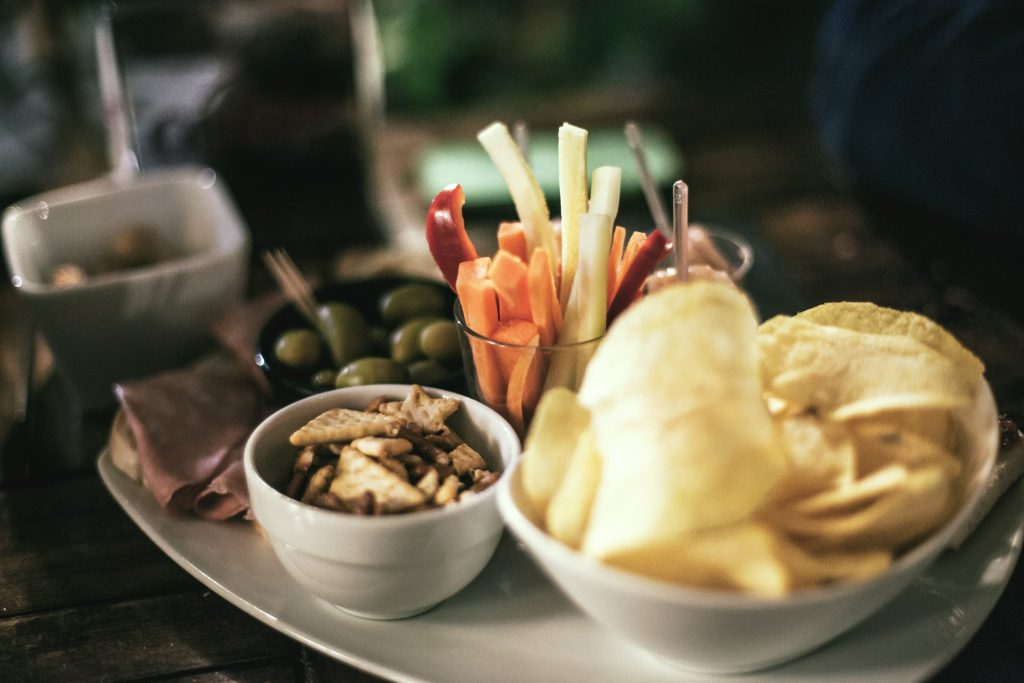 veggie snacks with chips and olives grapes crackers and veggie straws