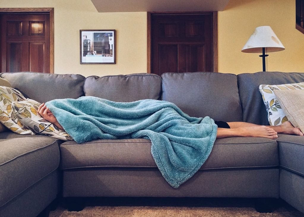 white woman hiding under blue blanket on grey gray sectional couch sick at home watching super bowl