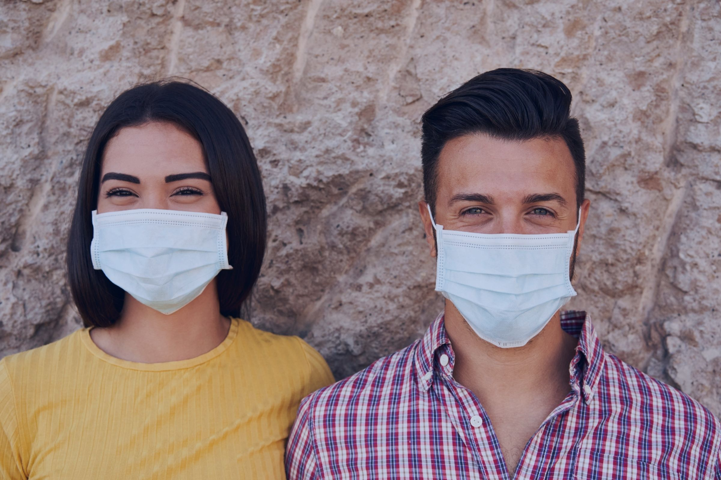 white couple smiling and standing next to each other wearing masks one woman and one man