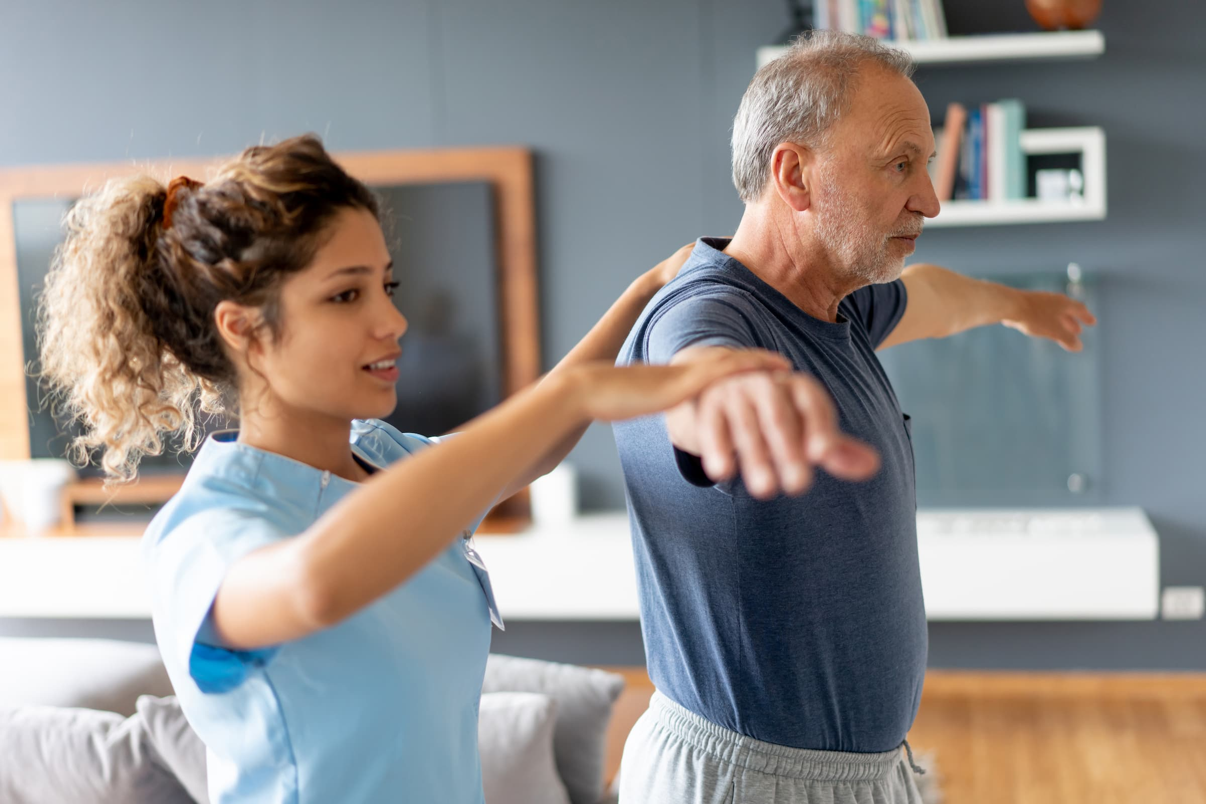 hispanic physical therapist helping elderly senior white man do physical therapy arm stretch movements