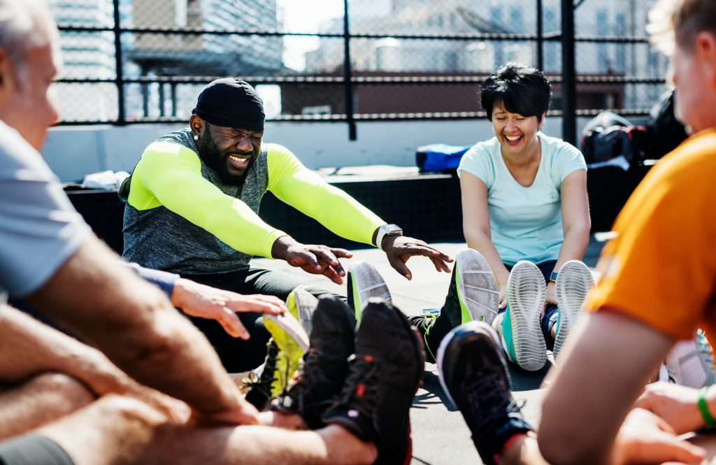 group of people sitting in circle stretching and exercising, how to not get hurt while exercising, warm-up and cool-down stretching muscles