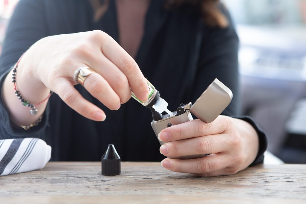 young adult woman filling vape mod e-cigarette with vape juice