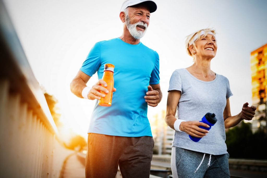 active seniors older man in blue shirt and yellow water bottle with wife who has blue water bottle and gray shirt smiling with sun setting behind them while they're walking outside