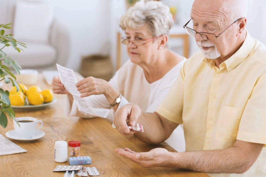 elderly white couple dividing up medicine for diabetes management