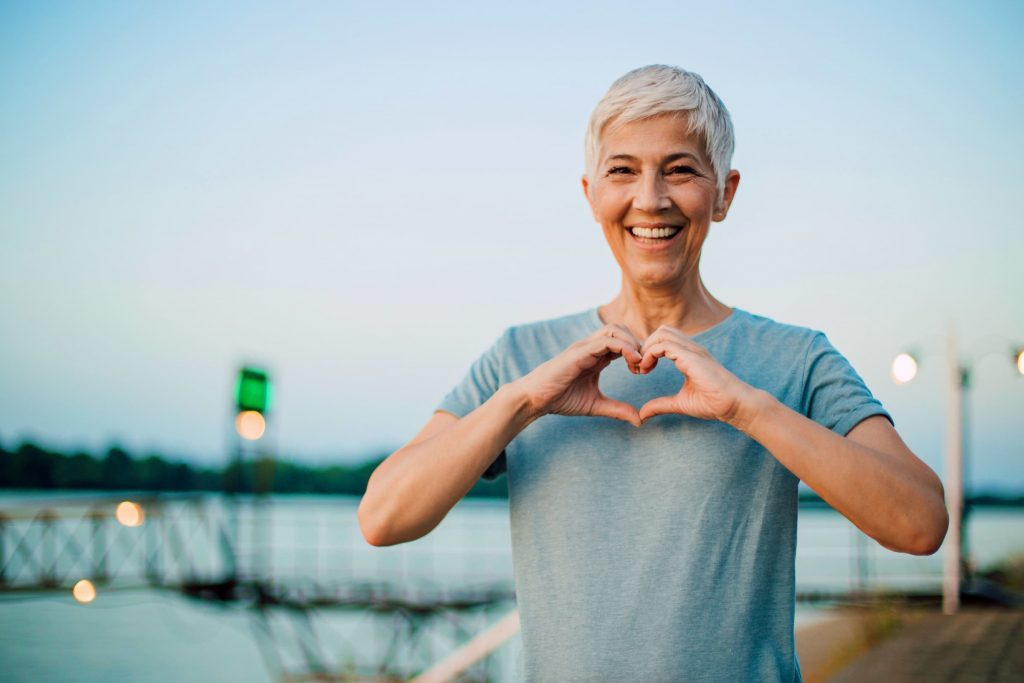 white elder woman with white hair making heart shaped hands on her chest wearing gray shirt standing outside next to water and street sign