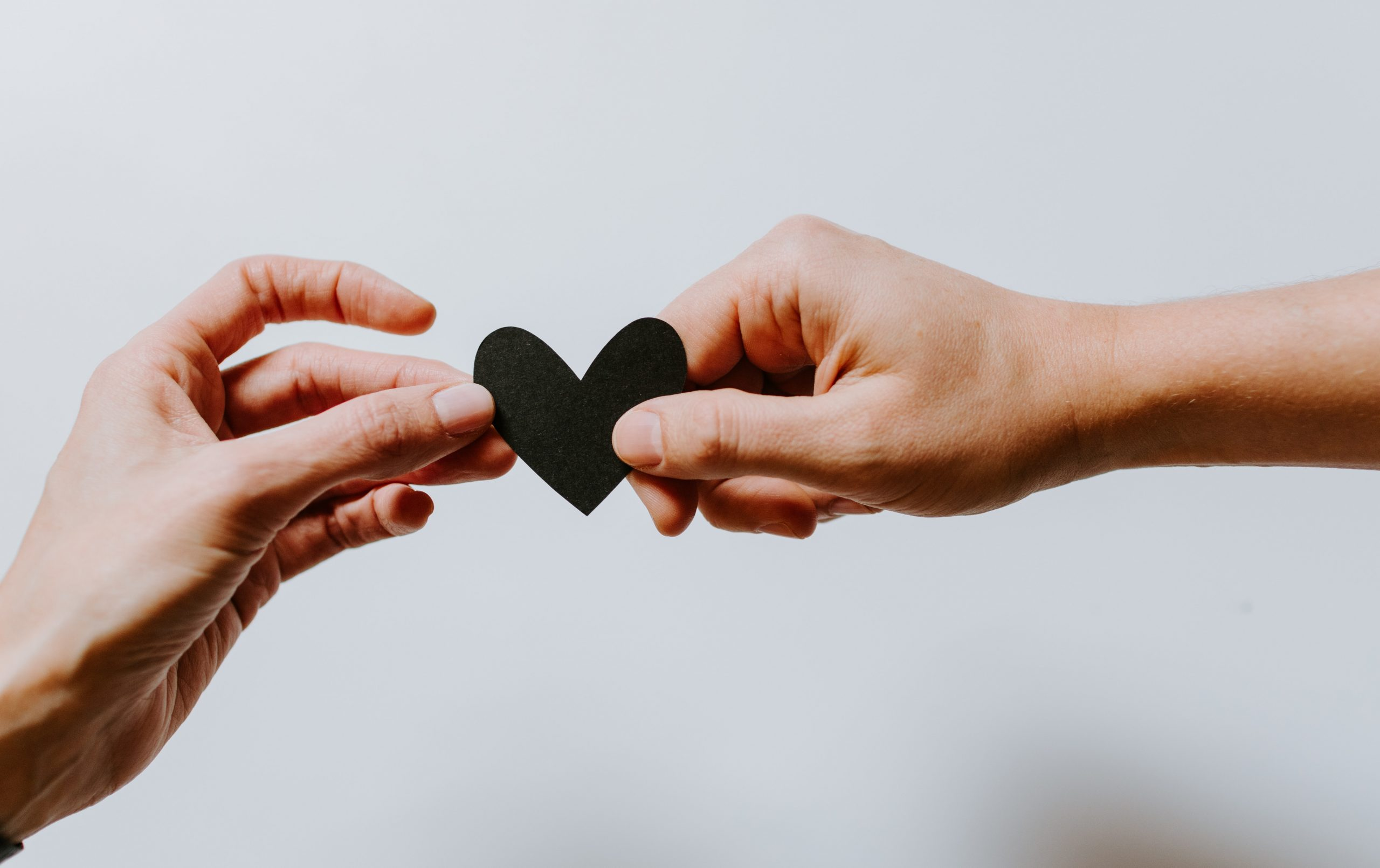 two white people hands holding black heart and sharing donation donate