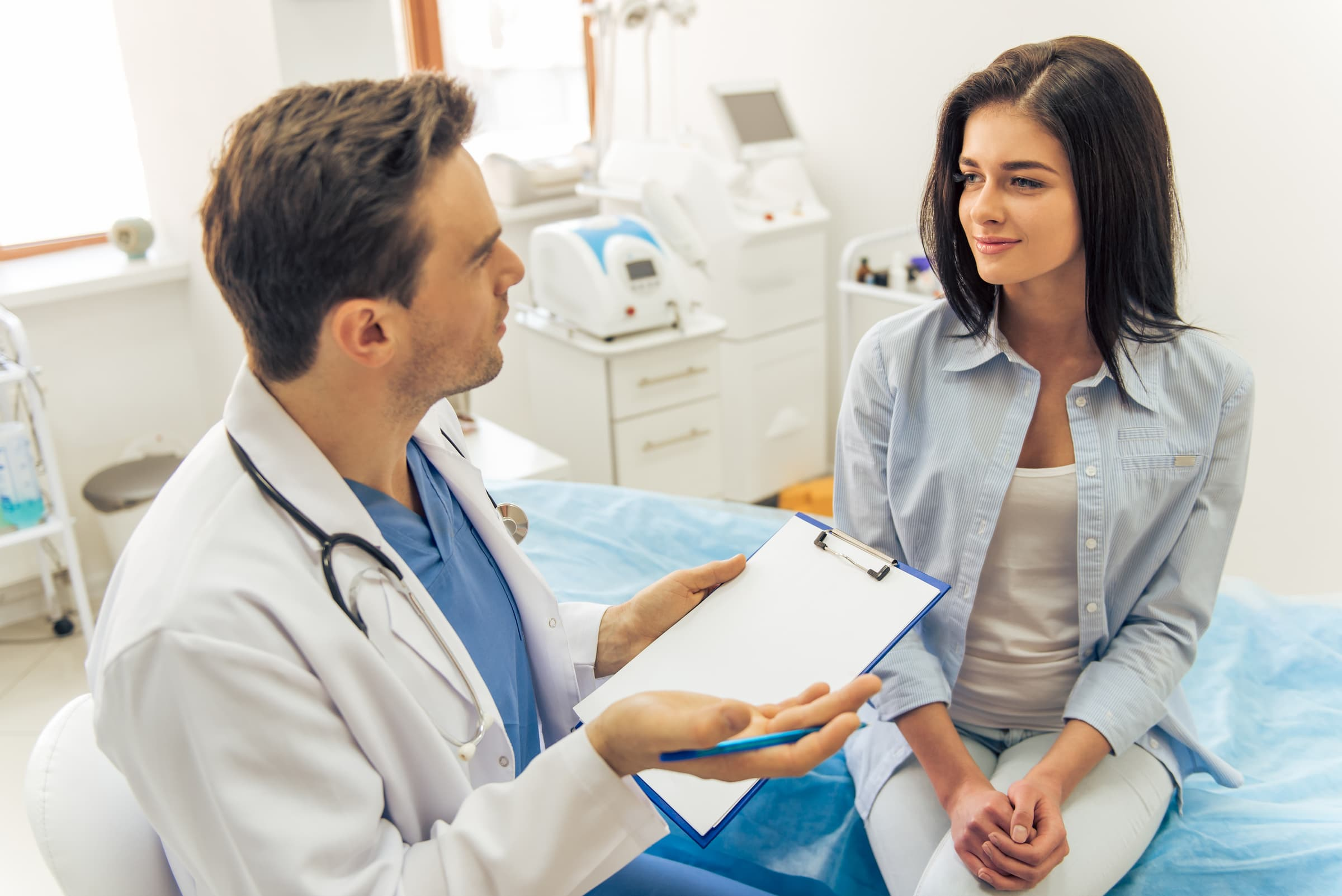 Handsome doctor is talking with young female patient and making notes while sitting in his office, clinic, family medicine, gynecology