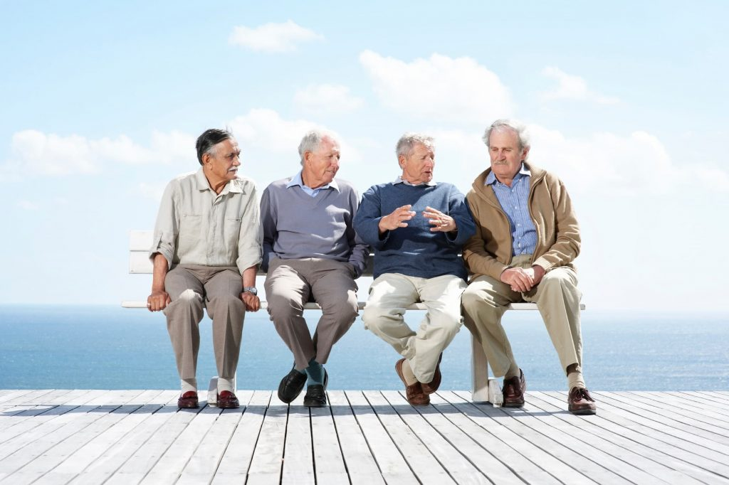 four senior men sitting on a bench on a dock with the ocean and sky behind them