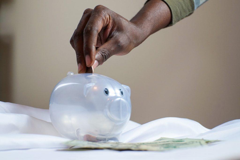 black man putting money into a clear pig-shaped piggy bank