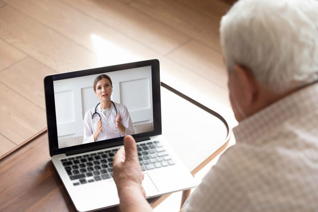 white senior man doing telemedicine visit with female brunette doctor on laptop macbook air