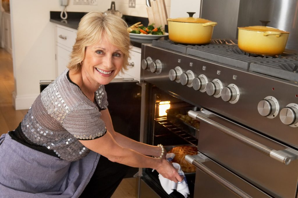 white senior woman getting pie out of the oven