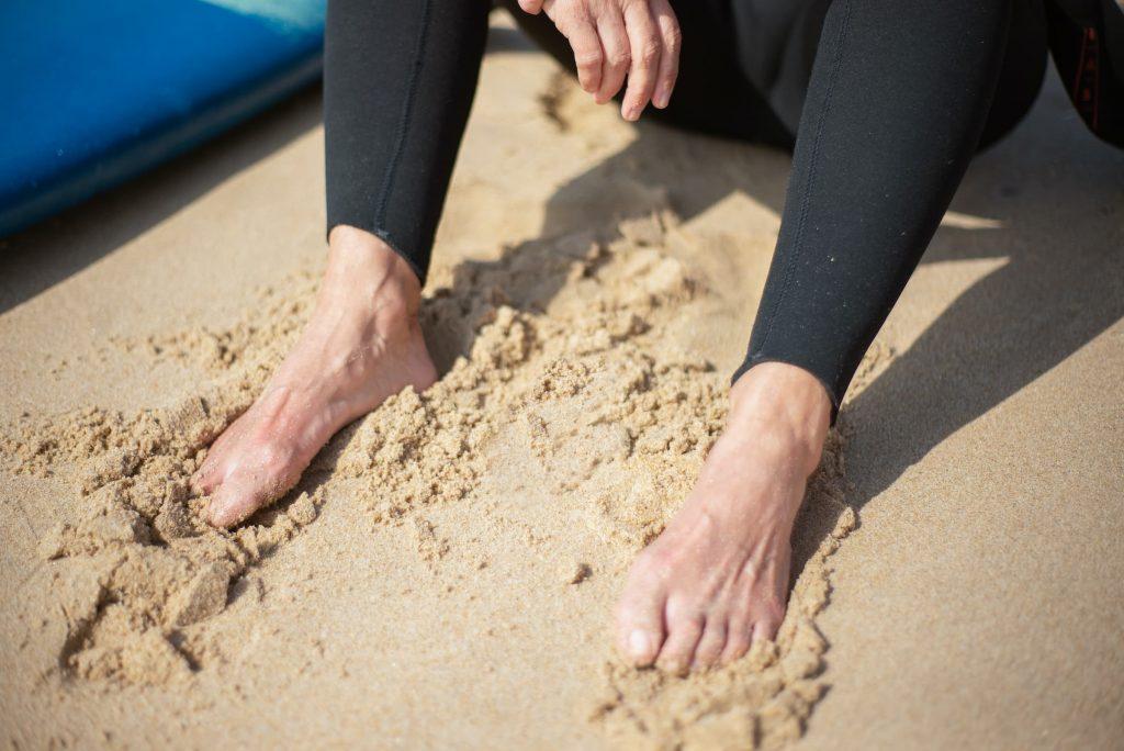white senior woman in black leggings with feet in sand, summer fun diabetic feet cdc checklist