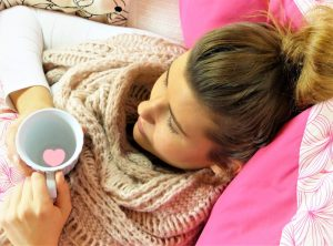 young woman in bed wrapped in warm blanket holding a cup of warm liquid, possibly ill or sick