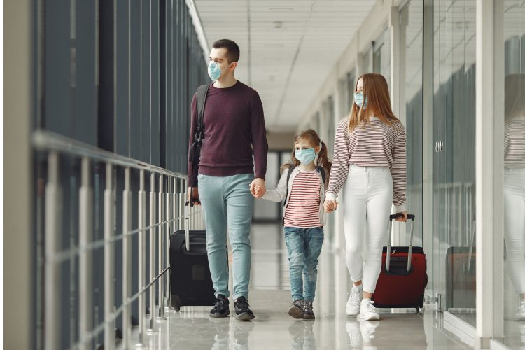 family walking through airport with masks on covid-19 vaccine travel after getting vaccine