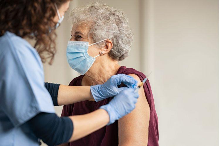 older woman getting covid-19 vaccine elderly woman black nurse
